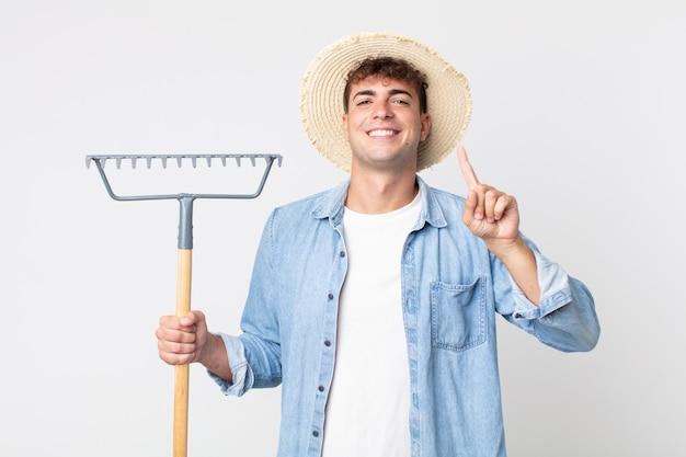 Homem jovem bonito sorrindo e parecendo amigável, mostrando o número um. conceito de fazendeiro