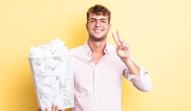 Homem jovem bonito sorrindo e parecendo feliz, gesticulando vitória ou paz. conceito de lixo de bolas de papel