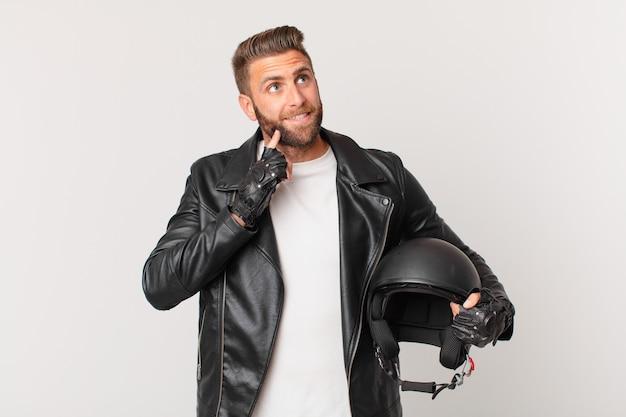 Homem jovem bonito sorrindo feliz e sonhando acordado ou duvidando. conceito de capacete de motocicleta