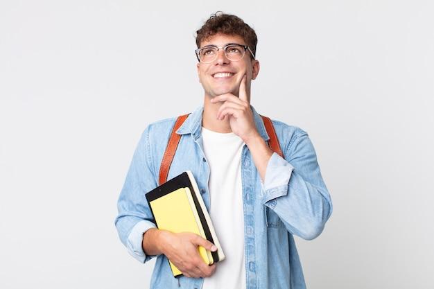 Homem jovem bonito sorrindo feliz e sonhando acordado ou duvidando. conceito de estudante universitário