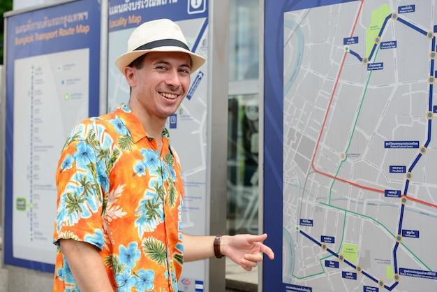 Homem jovem bonito turista feliz verificando o mapa na estação de metrô ao ar livre