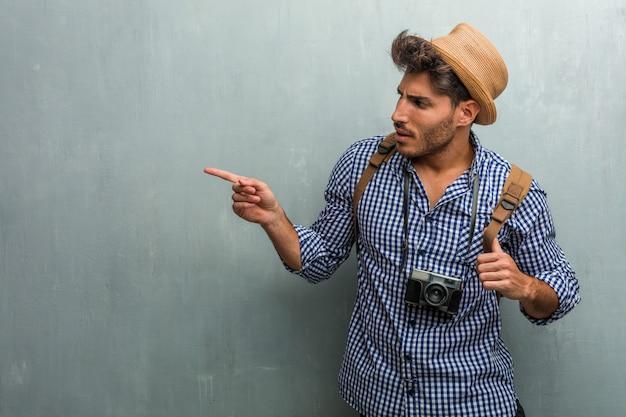 Homem jovem bonito viajante usando um chapéu de palha, uma mochila e uma câmera fotográfica apontando para o lado