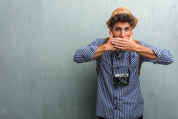 Homem jovem bonito viajante usando um chapéu de palha, uma mochila e uma câmera fotográfica cobrindo a boca