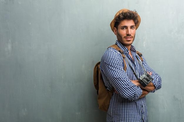 Homem jovem bonito viajante usando um chapéu de palha, uma mochila e uma câmera fotográfica cruzando os braços