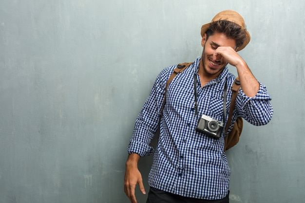 Homem jovem bonito viajante usando um chapéu de palha, uma mochila e uma câmera fotográfica rindo e se divertindo