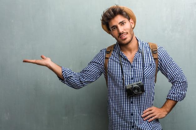 Homem jovem bonito viajante usando um chapéu de palha, uma mochila e uma câmera fotográfica segurando algo com as mãos