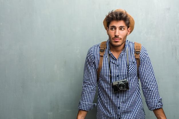Homem jovem bonito viajante usando um chapéu de palha, uma mochila, encolher os ombros