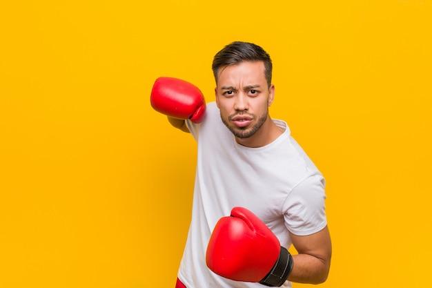 Homem jovem boxeador sul-asiático usando luvas vermelhas.