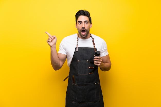 Homem jovem cabeleireiro sobre fundo amarelo isolado surpreso e apontando o dedo para o lado