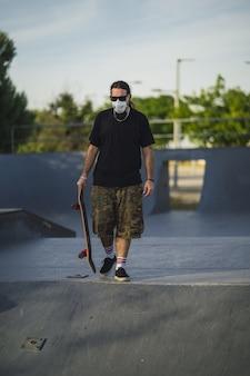 Homem jovem caminhando em um parque com um skate e uma máscara facial médica - conceito covid-19