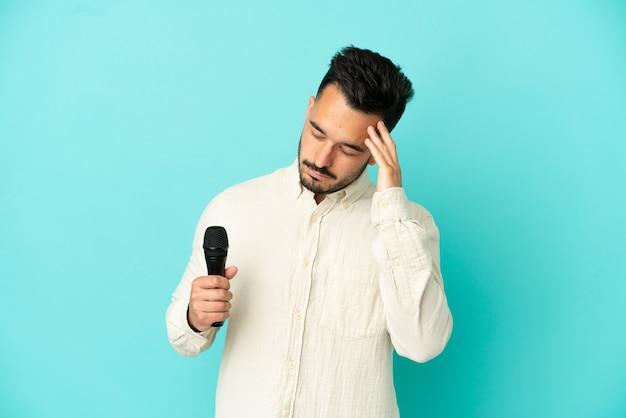 Homem jovem cantor caucasiano isolado em um fundo azul com dor de cabeça
