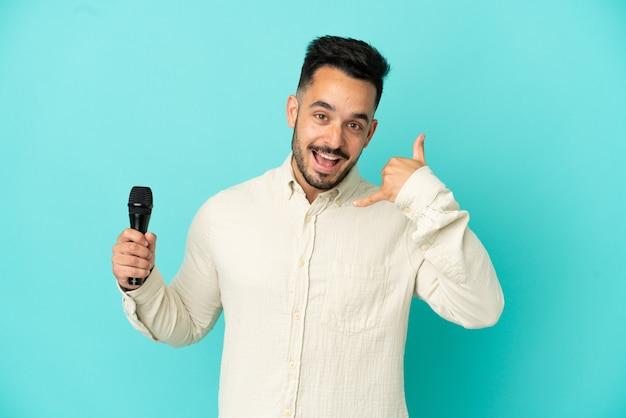Homem jovem cantor caucasiano isolado em um fundo azul, fazendo gesto de telefone. ligue-me de volta sinal