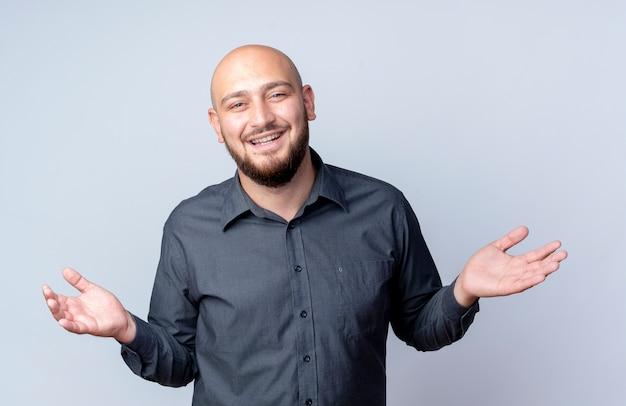 Homem jovem careca alegre do call center mostrando as mãos vazias isoladas no branco