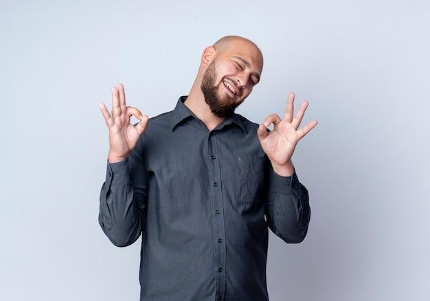Homem jovem careca alegre do call center piscando e fazendo sinais de ok, isolado no branco