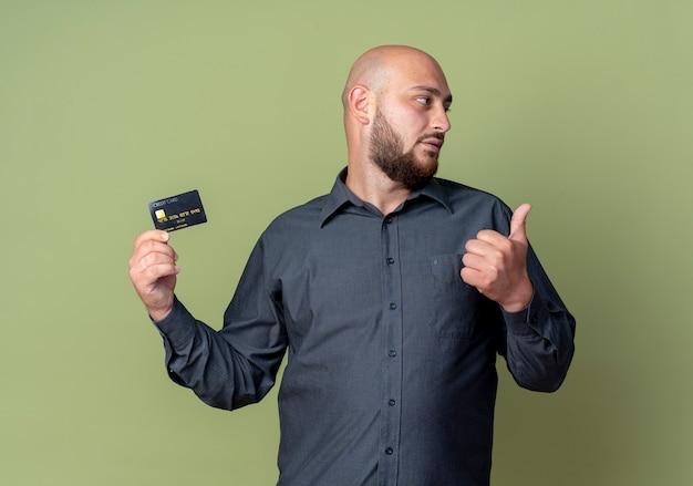 Homem jovem careca de call center segurando um cartão de crédito, mostrando o polegar para cima e olhando para o lado isolado em fundo verde oliva
