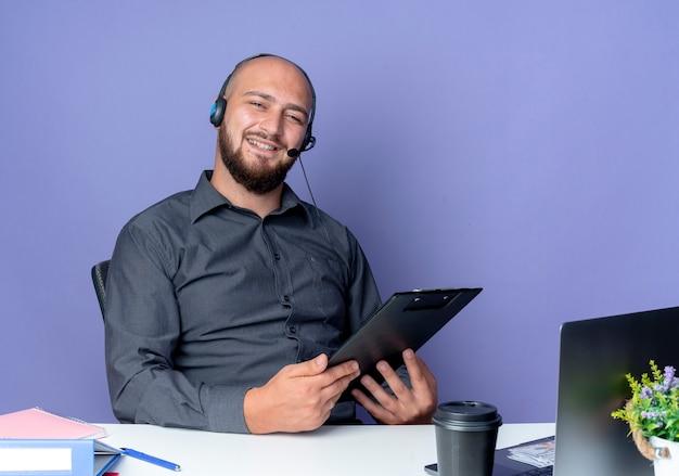 Homem jovem careca de call center usando fone de ouvido, sentado na mesa com ferramentas de trabalho isoladas em um fundo roxo