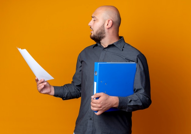 Homem jovem careca de call center virando a cabeça para o lado com os olhos fechados, segurando uma pasta e um documento isolado em um fundo laranja