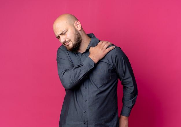 Homem jovem careca dolorido de call center colocando a mão no ombro com os olhos fechados, isolado em vermelho com espaço de cópia