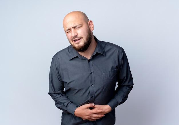 Homem jovem careca dolorido de call center segurando a barriga, sofrendo de dor com os olhos fechados, isolado no branco com espaço de cópia