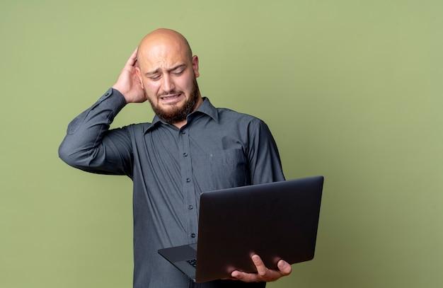 Homem jovem careca irritado de call center segurando e olhando para um laptop com a mão na cabeça isolada em verde oliva com espaço de cópia