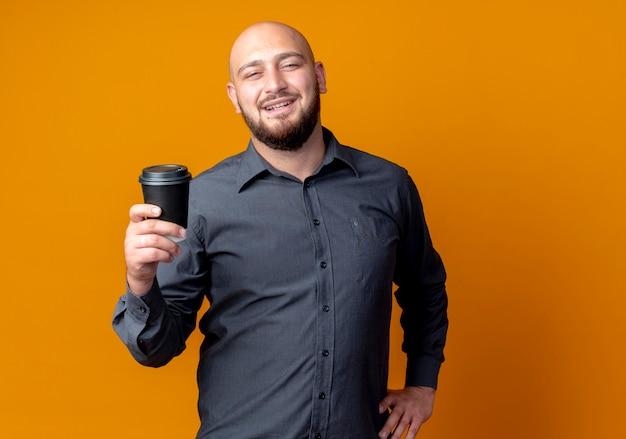 Homem jovem careca sorridente de call center segurando uma xícara de café de plástico e colocando a mão na cintura isolada na parede laranja