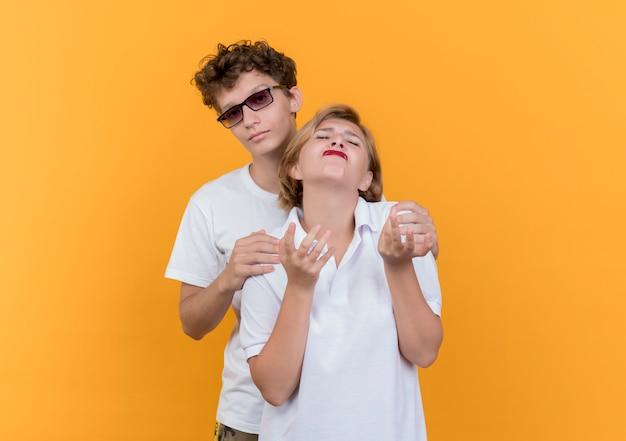 Homem jovem casal tentando abraçar a namorada descontente e chateada em pé sobre a parede laranja