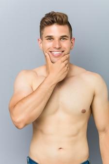 Homem jovem caucasiano fitness sem camisa tocando seu queixo