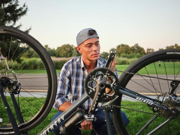 Homem jovem caucasiano que parece estar concentrado enquanto verifica os pedais de sua bicicleta, ajoelhado sobre ela