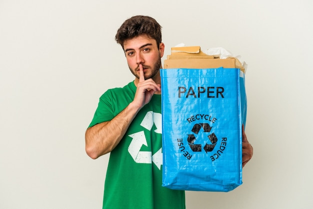Homem jovem caucasiano reciclando papelão isolado no fundo branco, mantendo um segredo ou pedindo silêncio.