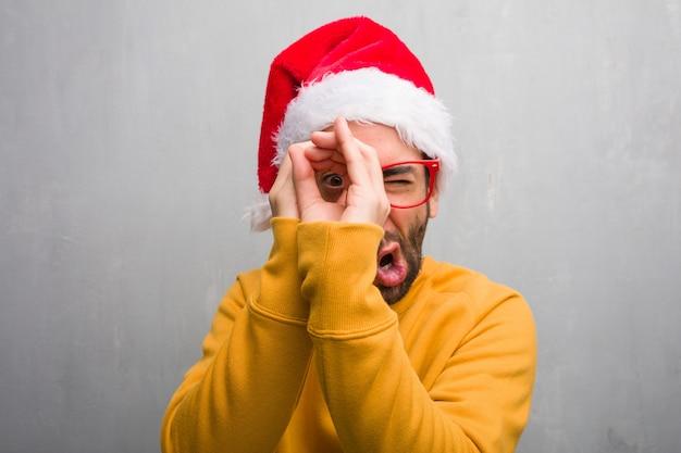 Homem jovem, celebrando, dia natal, presentes segurando, fazendo, a, gesto, de, um, spyglass