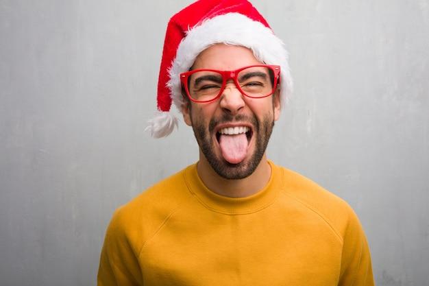 Homem jovem, celebrando, dia natal, presentes segurando, funnny, e, amigável, mostrando, língua