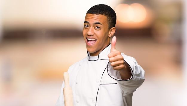 Homem jovem chef afro-americano, dando um polegar para cima gesto, porque algo de bom aconteceu na parede fora de foco