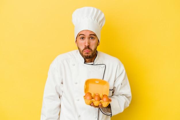 Homem jovem chef caucasiano segurando ovos isolados em fundo amarelo encolhe os ombros e abre os olhos confusos.