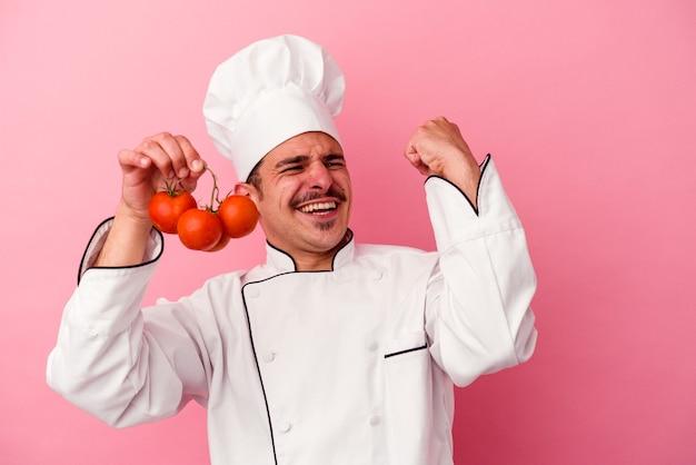 Homem jovem chef caucasiano segurando tomates isolados no fundo rosa, levantando o punho após uma vitória, o conceito de vencedor.
