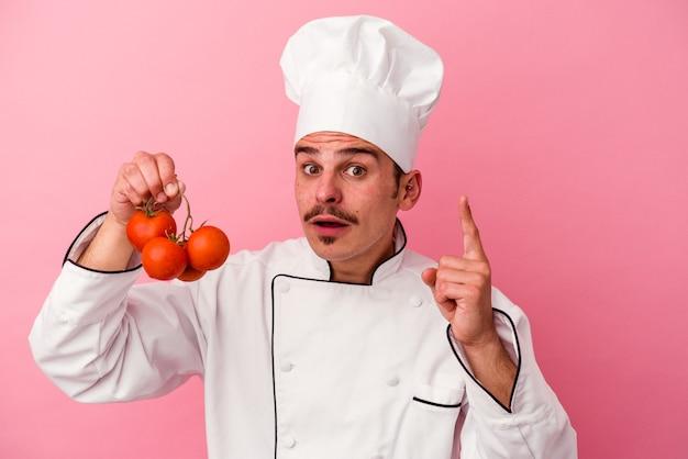 Homem jovem chef caucasiano segurando tomates isolados no fundo rosa, tendo uma ideia, o conceito de inspiração.