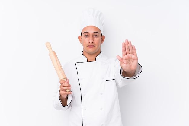 Homem jovem chef latina em pé com a mão estendida, mostrando o sinal de stop, impedindo-o.