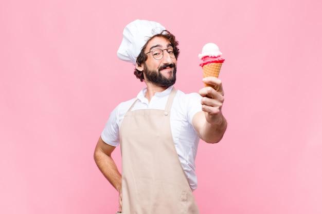 Homem jovem chef louco com um sorvete contra parede rosa