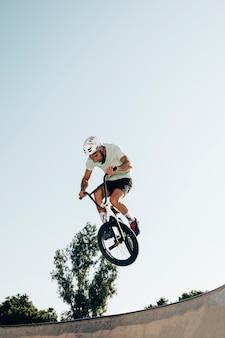 Homem jovem, ciclismo, em, skatepark, tiro baixo ângulo