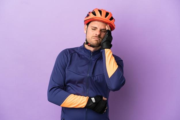 Homem jovem ciclista brasileiro isolado em fundo roxo com dor de cabeça
