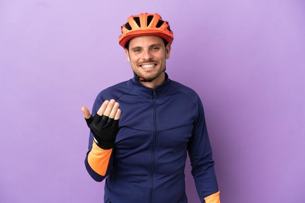 Homem jovem ciclista brasileiro isolado no fundo roxo, convidando para vir com a mão. feliz que você veio