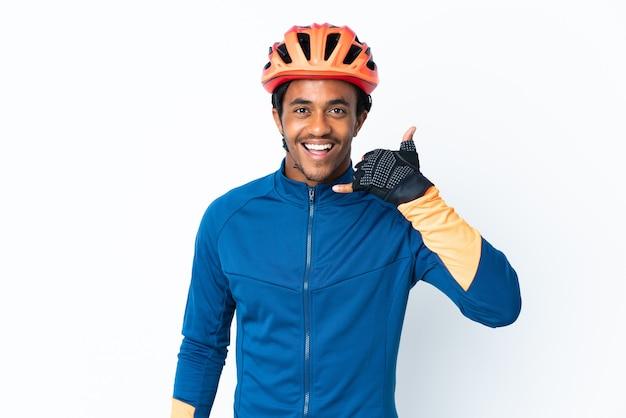 Homem jovem ciclista com tranças sobre fundo isolado, fazendo gesto de telefone. ligue-me de volta sinal