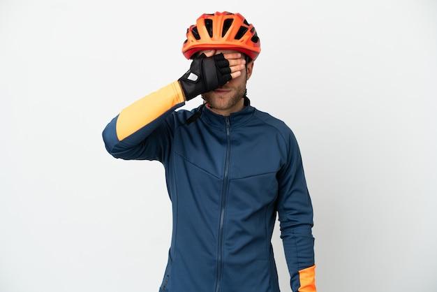 Homem jovem ciclista isolado cobrindo os olhos com as mãos. não quero ver nada