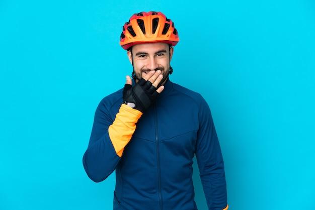 Homem jovem ciclista isolado em um fundo azul feliz e sorridente cobrindo a boca com a mão