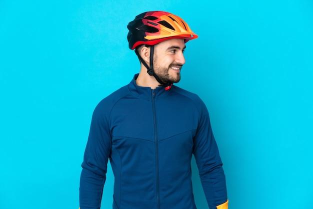 Homem jovem ciclista isolado em um fundo azul, olhando de lado