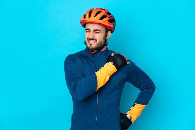 Homem jovem ciclista isolado em um fundo azul sofrendo de dores no ombro por ter feito um esforço