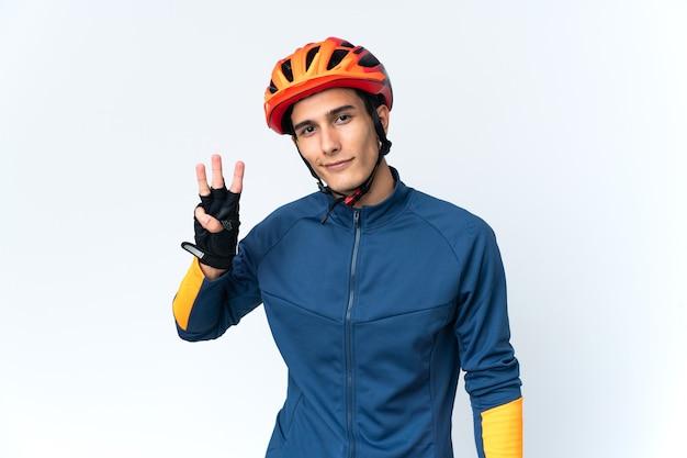 Homem jovem ciclista isolado em um fundo feliz e contando três com os dedos