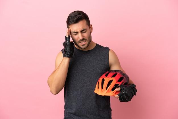 Homem jovem ciclista isolado em um fundo rosa com dor de cabeça
