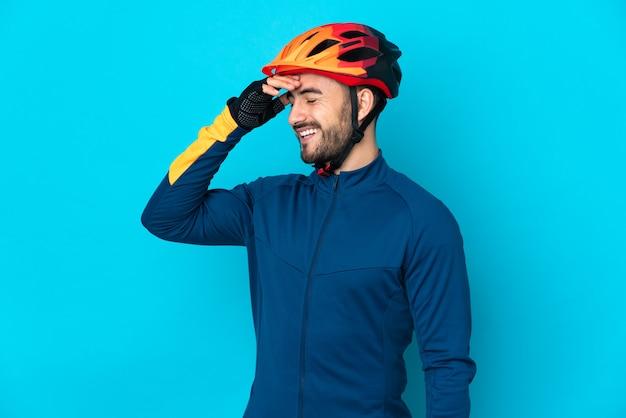 Homem jovem ciclista isolado na parede azul sorrindo muito