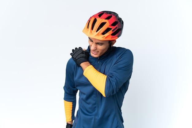 Homem jovem ciclista isolado na parede com dor no ombro por ter feito esforço