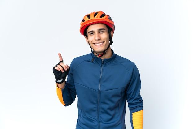 Homem jovem ciclista isolado na parede mostrando e levantando um dedo em sinal dos melhores